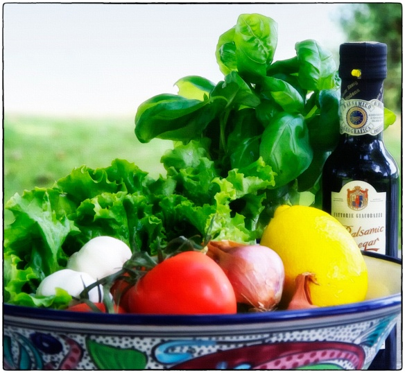 In the box: leafy lettuce, basil, bottle of wine, large basket, balsamic vinegar, patterned serving bowl, tomatoes, garlic, shallots, box of spaghetti, wooden spoon
